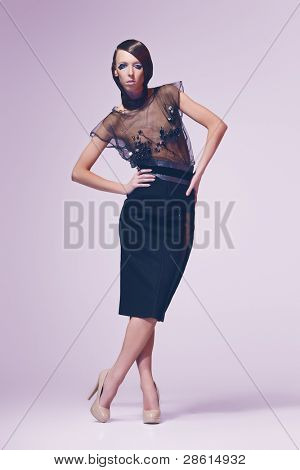 Young brunette lady in dress posing on pink background