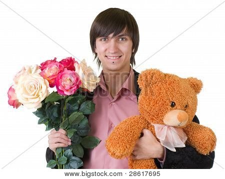 Young man with flowers and teddy bear