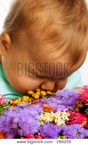 Cute Baby With A Bunch Of Flowers.