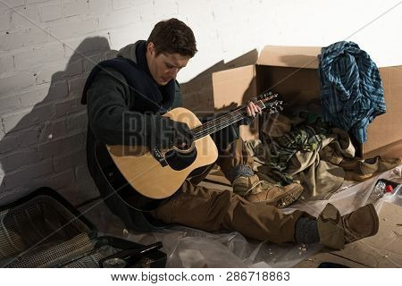 Homeless Man Holding Guitar While