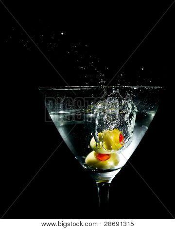 Two Olives Splashing Into Martini Glass