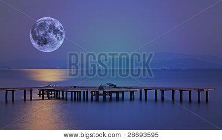 Exposición prolongada en el muelle de madera con luz de la luna