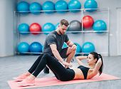 Trainer Helping Young Woman To Do Abdominal Exercises On The Background Of Fitness Balls. Beautiful  poster