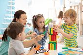 Little Kids Build Wooden Toys At Home Or Daycare. Kids Playing With Color Blocks. Educational Toys F poster