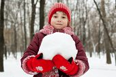foto of ruddy-faced  - Little girl with a snowball in his hands against the tree - JPG