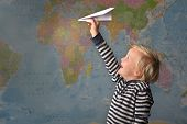 A Young Blonde Boy Flies A Paper Plane In Front Of A Large World Map poster