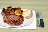 stock photo of baked potato  - Rib steak with mushrooms and baked potato on a green tablecloth - JPG