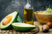 Avocado And Avocado Oil On A Wooden Background. poster