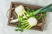 Fresh Florence Fennel Bulbs Or Fennel Bulb, Leek And Parsley In Wooden Box With Dried Grass On Light poster