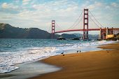 Golden Gate Bridge With Birds Walking Along The Shoreline Of Soft Breaking Waves Along The Northern  poster
