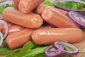 stock photo of raw chicken sausage  - Raw hot dog sausage with lettuce and onion on wooden board - JPG
