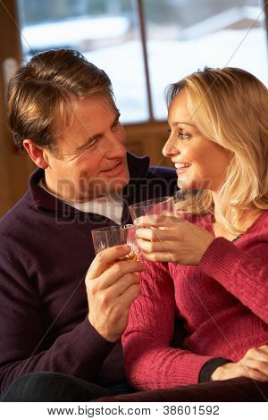 Middle Aged Couple Sitting On Sofa With Glasses Of Whisky