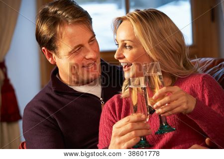 Middle Aged Couple Sitting On Sofa With Glasses Of Champagne