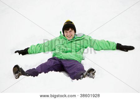 Teenage Boy Making Snow Angel On Slope