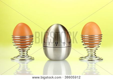egg timer and egg in metal stand on green background