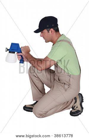 Man using paint spraying device