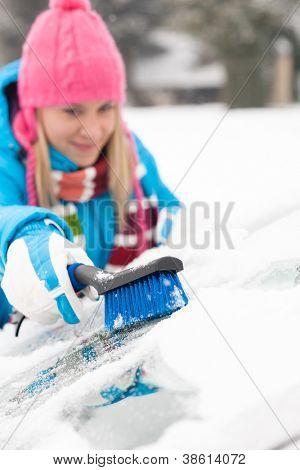 Woman wiping car windshield using brush snow winter happy work