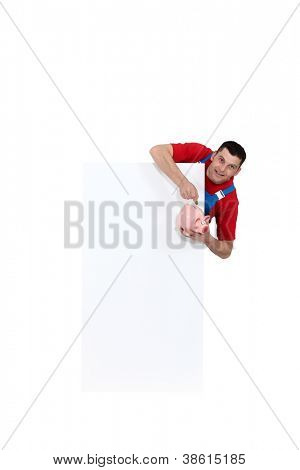 Tradesman pointing to a piggy bank and standing beside a blank sign