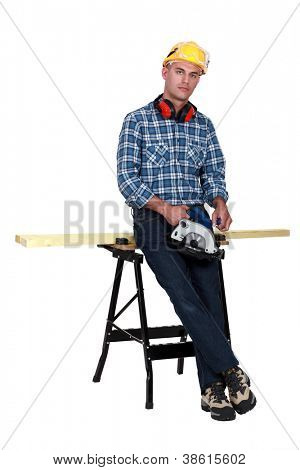 Tradesman standing in front of a workbench and holding a circular saw