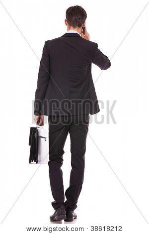Vista posterior de un hombre de negocios con un maletín y hablando en su teléfono inteligente sobre fondo blanco