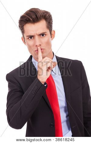 business man with finger on his lips making the quiet gesture