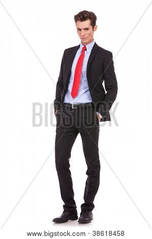 Proud business owner poses for a serious portrait on white background. Full body picture of a serious young business man looking at the camera