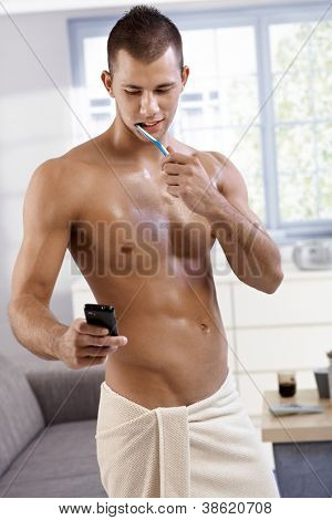 Sexy muscular semi-nude young man standing in towel in living room, washing teeth and using mobile phone, smiling.