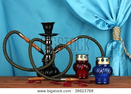 hookah on a wooden table on a background of blue curtain close-up