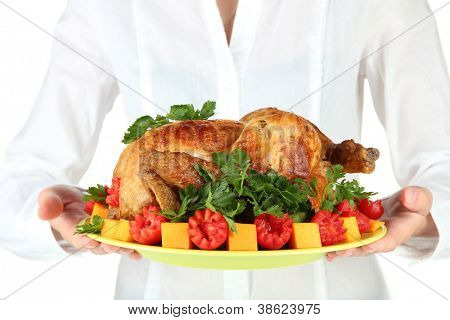 Chef holding a plate of baked chicken with vegetables close-up