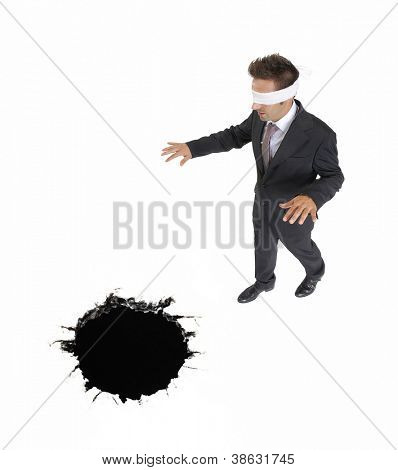 blindfold businessman approaching to a black hole.