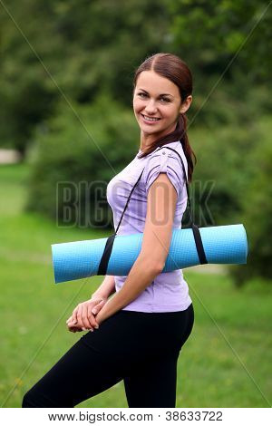 Young and beautiful girl with fitness mat in the park