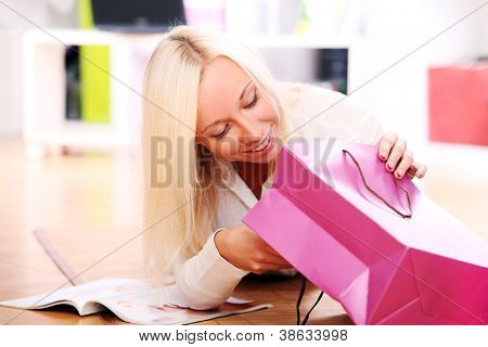 Young blonde relaxing at home and looking in a shooping bag