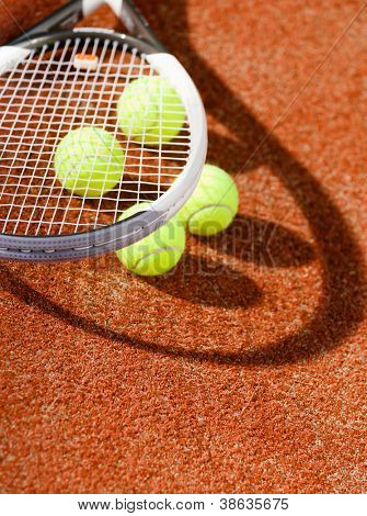 Close up view of tennis racquet and balls on the clay tennis court
