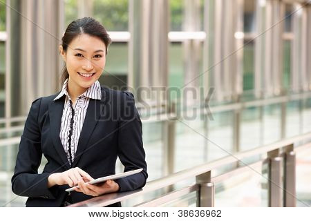 Chinese Businesswoman Working On Tablet Computer Outside Office