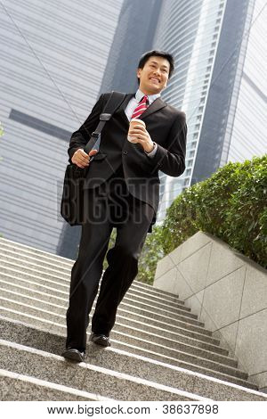 Chinese Businessman Rushing Down Steps Carrying Bag And Takeaway Coffee