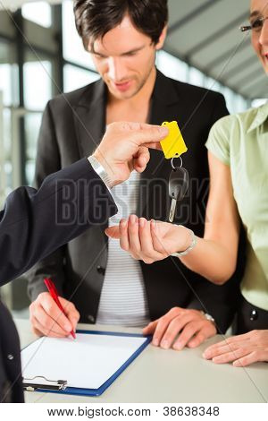 Man handing keys to new car to woman, her man signing the sales or rental contract
