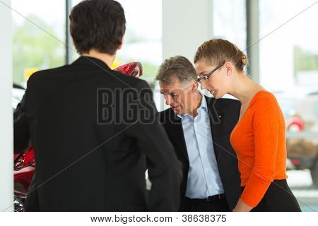 Mature single man with autos in light car dealership with a young couple, man and woman, looking beneath the hood he obviously is buying a car or is a car dealer