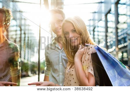 Couple shopping in the free time in the sun with shopping bag