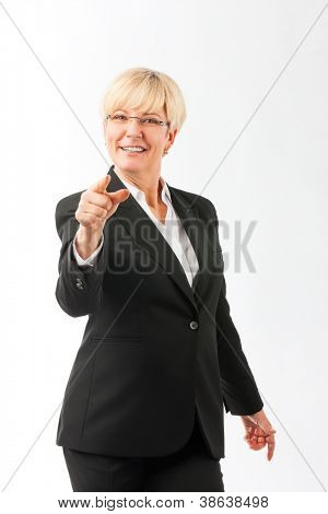 Mature woman point finger on the viewer, studio shoot
