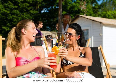 People at beach drinking having a party, two girls clinking glasses with cocktails having fun