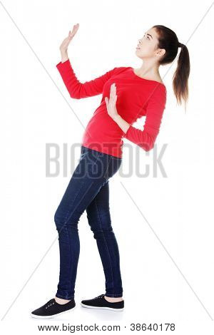 Scared young woman afraid of something above her, isolated on white