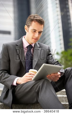 Businessman Working On Tablet Computer Outside Office With Takeaway Coffee