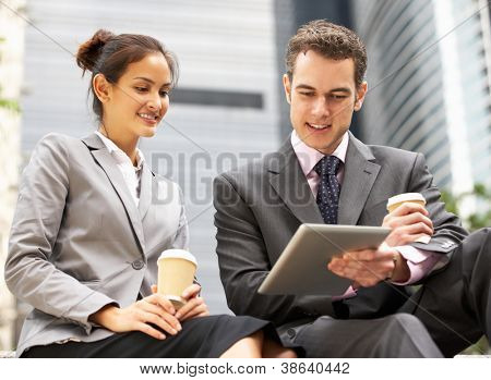 Businessman And Businesswoman Using Digital Tablet Outside Office