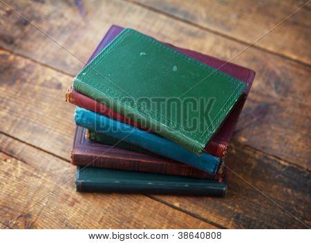 Old books on old wooden desk.