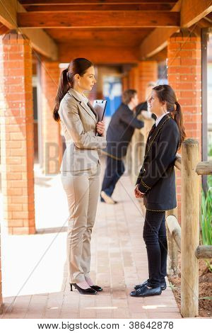 high school teacher talking to student by school corridor