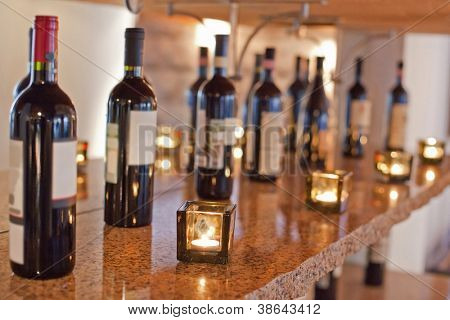 Bottles of wine, candles are on shelf