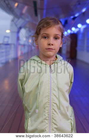 Little girl standing on deck of large passenger ship