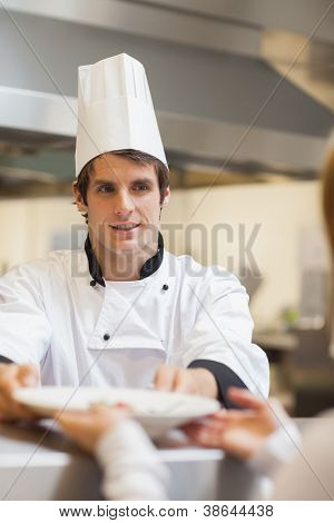 Chef passing plate to waitress at order station in kitchen