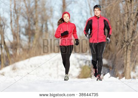 Sport couple running in winter. Runners jogging in snow in city park. Interracial young happy couple enjoying healthy lifestyle. Asian woman fitness model and caucasian man.