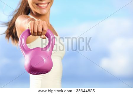 Kettlebells. Kettlebell training fitness woman - closeup of hand lifting kettlebell outside against blue sky with copy space.